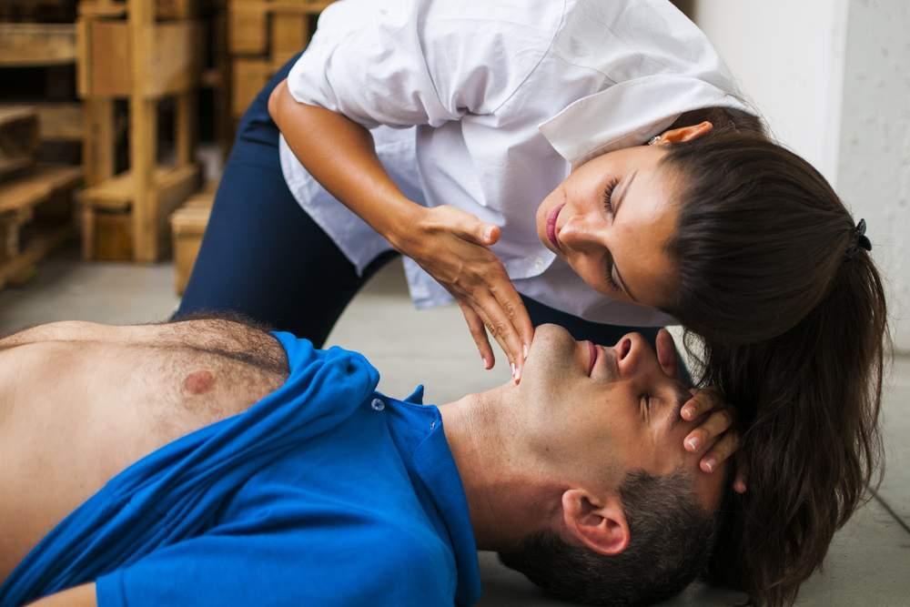 Mujer aplicando procedimiento de soporte vital básico en paciente